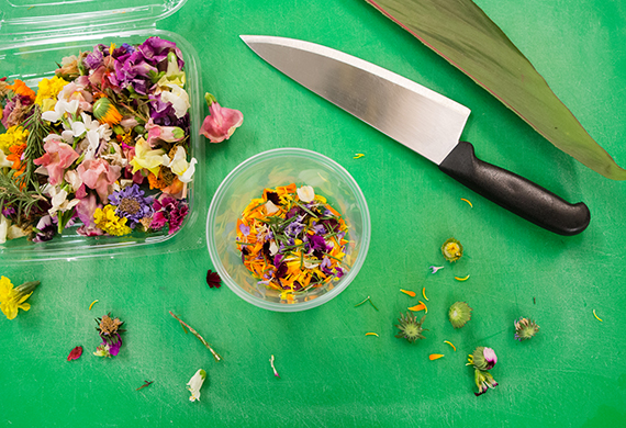 Cutting board with a knife and edible flowers.