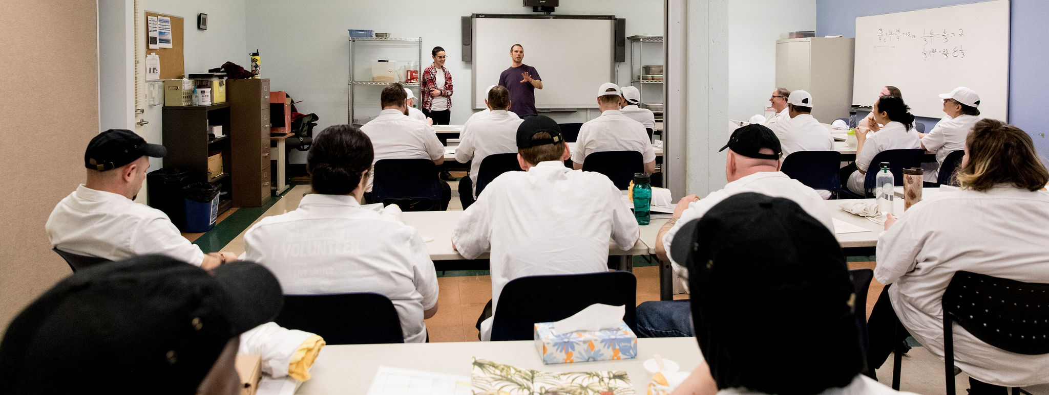 A large group of students in a classroom listening to two instructors