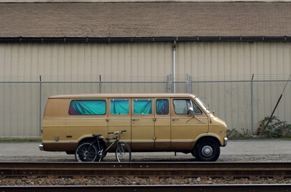 A van parked near railroad tracks serves as a home for someone experiencing homelessness